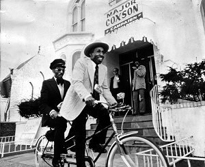 Major Coxson rides a tandem bicycle with his chauffeur, Quinzelle Champagne, in front of Coxson's campaign headquarters in 1972 (his fleet of vehicles had been seized by the IRS).